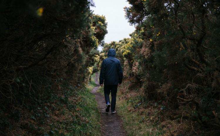 un hombre caminando a travéz de un sendero